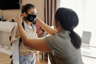 A mom puts on her child's pandemic mask